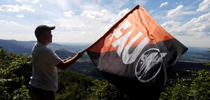 Mann mit FAU-Fahne auf dem Boßler mit guter Aussicht.